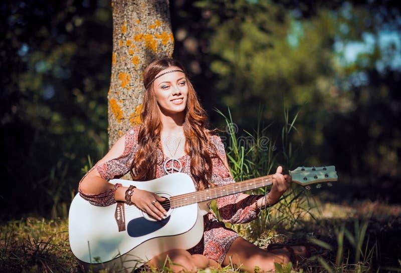 Muchacha joven hermosa del hippie que se sienta debajo del árbol y que toca la guitarra imagenes de archivo