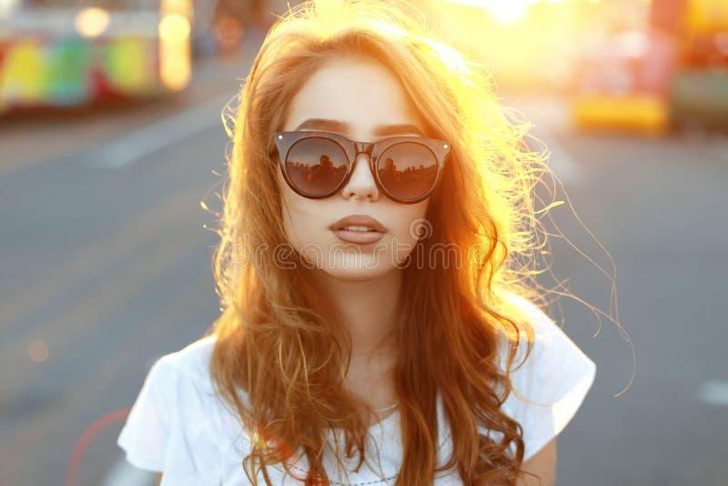 Muchacha joven hermosa del inconformista en la colocación de moda de las gafas de sol fotografía de archivo libre de regalías