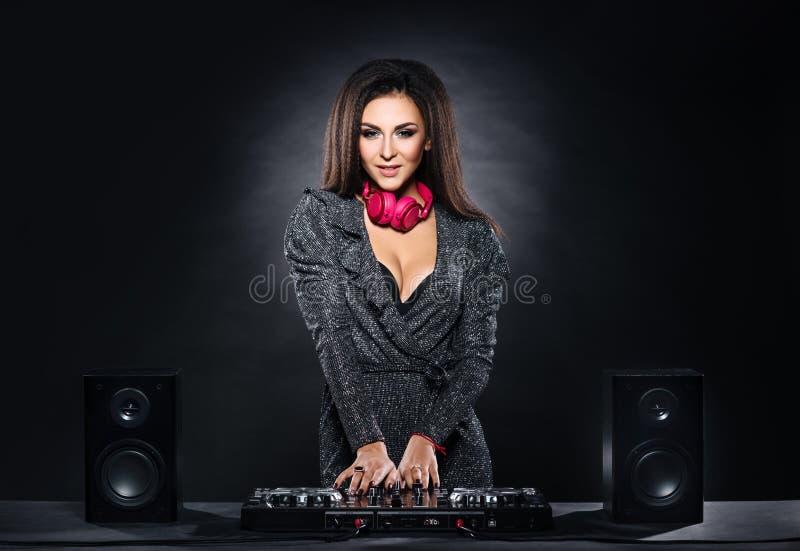 Muchacha joven, hermosa y atractiva de DJ que juega música en un partido de disco en un club de noche foto de archivo