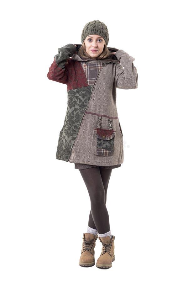 Muchacha joven linda bonita del inconformista con la gorrita tejida que pone en sudadera con capucha de la capa encapuchada en ro fotografía de archivo