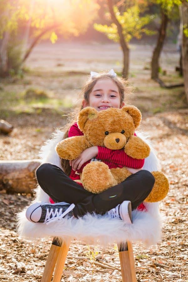 Muchacha joven linda de la raza mixta que abraza a Teddy Bear Outdoors fotos de archivo libres de regalías
