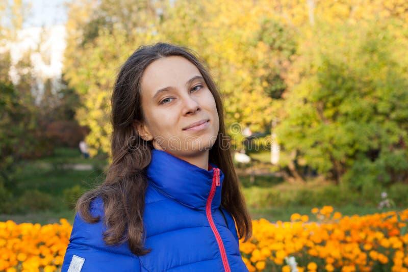 Muchacha joven 20s en la chaqueta azul que mira la cámara en de oro amarillo fotos de archivo libres de regalías