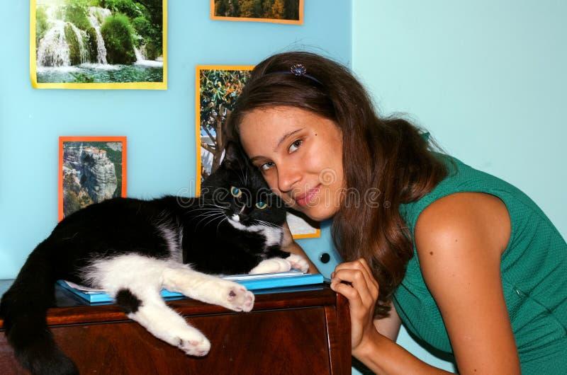 Muchacha joven 20s y gato blanco y negro que miran la cámara, él imagen de archivo libre de regalías