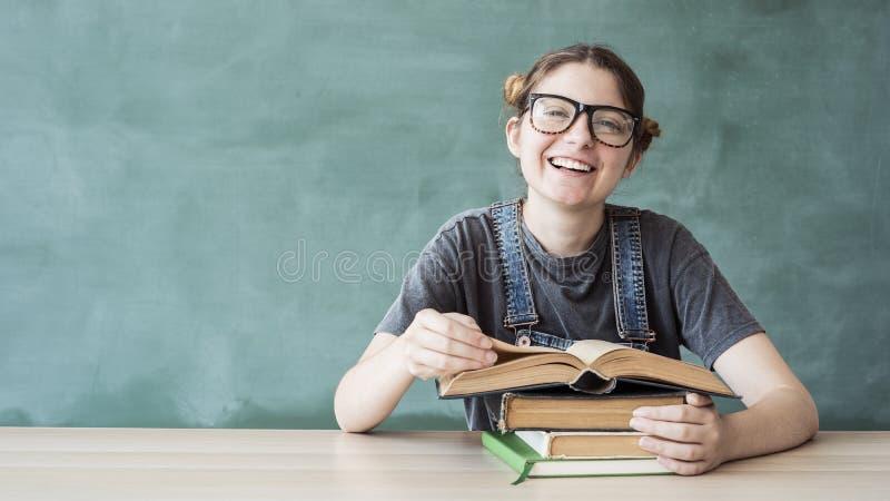Muchacha joven sonriente del estudiante con los libros imagen de archivo libre de regalías