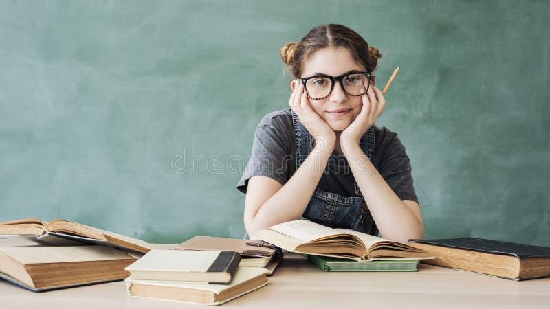 Muchacha joven sonriente del estudiante con los libros imágenes de archivo libres de regalías