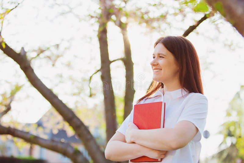 Muchacha joven sonriente del estudiante que sostiene un libro en campus imagen de archivo