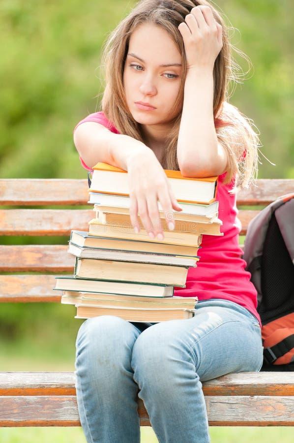 Muchacha joven triste del estudiante que se sienta en banco con los libros imagen de archivo