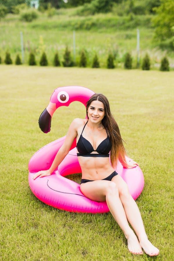 Muchacha joven y atractiva que se divierte y que ríe y que se divierte en la hierba cerca de la piscina en un flamenco rosado inf foto de archivo libre de regalías