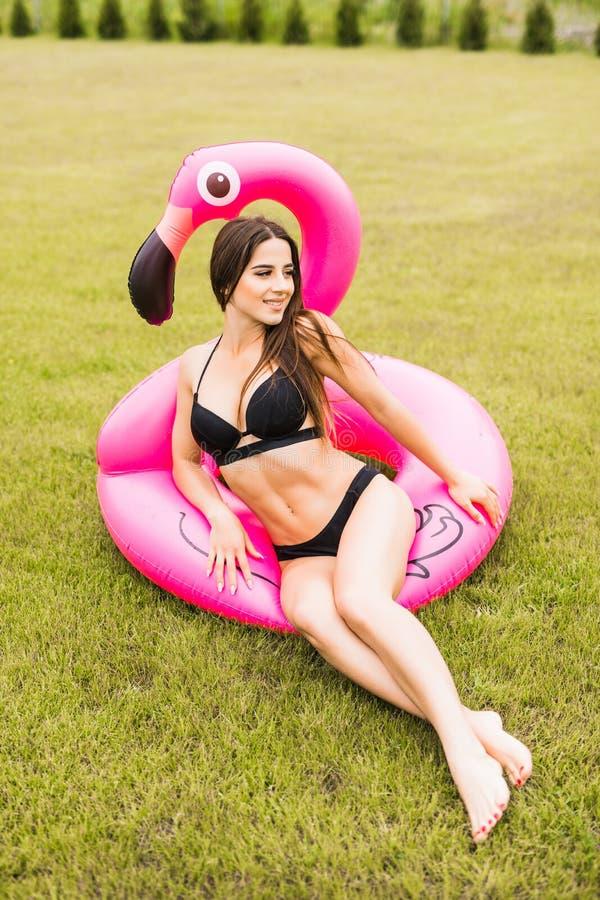 Muchacha joven y atractiva que se divierte y que ríe y que se divierte en la hierba cerca de la piscina en un flamenco rosado inf fotografía de archivo libre de regalías