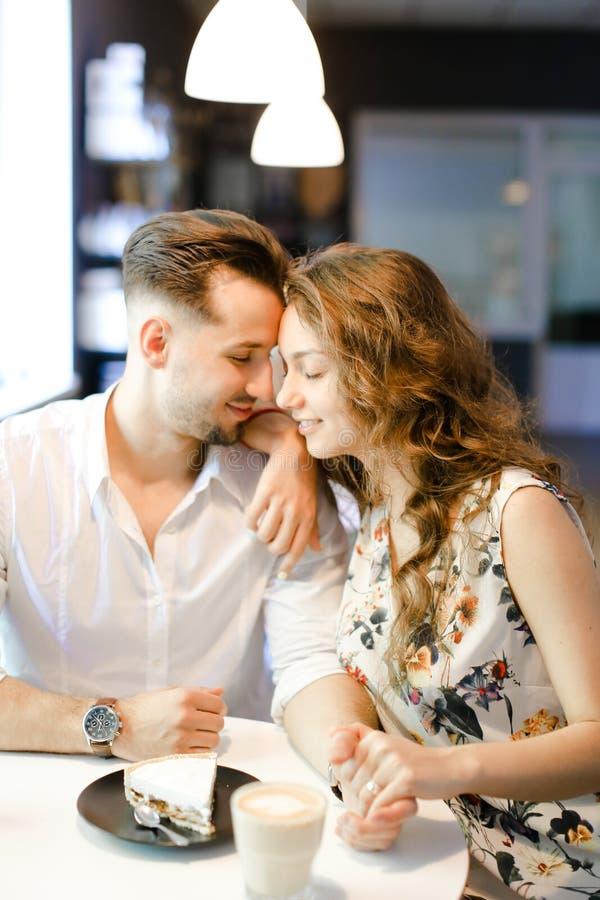 Muchacha joven y muchacho hermosos que se sientan en el café, el café de consumición y la reclinación fotos de archivo libres de regalías