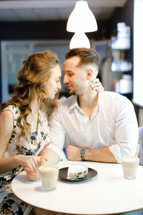 Muchacha joven y muchacho lindos que se sientan en el café, el café de consumición y la reclinación fotos de archivo libres de regalías
