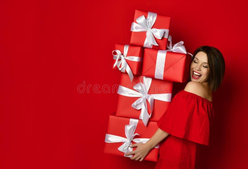 Muchacha jovial del cumpleaños en el vestido que presenta con los presentes fotografía de archivo