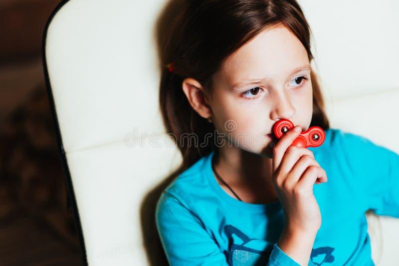 Muchacha a jugar con el hilandero que se sienta en una silla foto de archivo libre de regalías