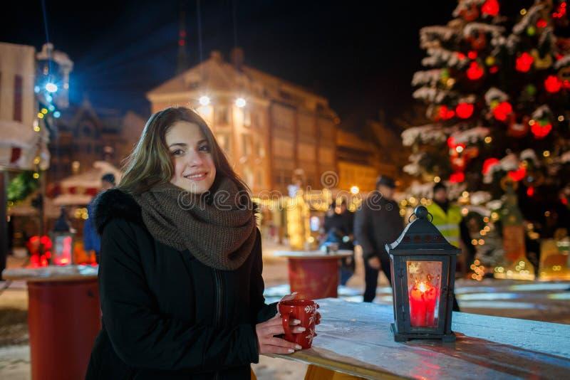 Muchacha larga del pelo en mercado europeo de la Navidad Mujer joven que disfruta de la estación de vacaciones de invierno Fondo  imágenes de archivo libres de regalías