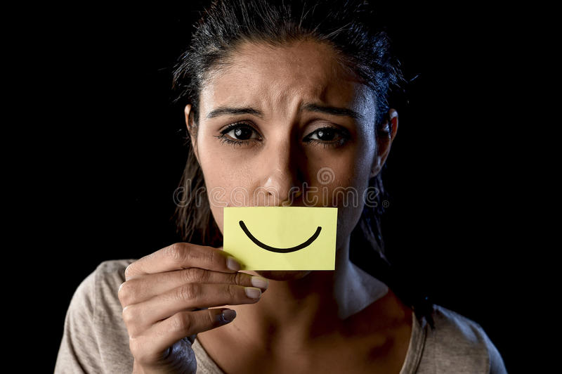 Muchacha latina deprimida triste latina que sostiene el papel que oculta su boca detrás de la sonrisa dibujada falsificación foto de archivo