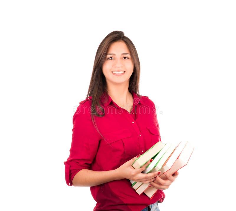 Muchacha latina joven que sostiene la pila de libros fotos de archivo libres de regalías