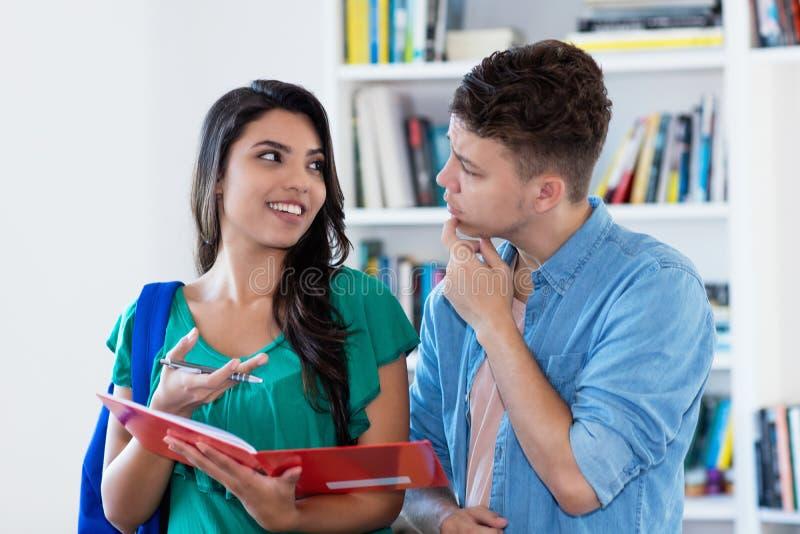 Muchacha latinoamericana que aprende con el estudiante masculino alemán en la sala de clase imagenes de archivo