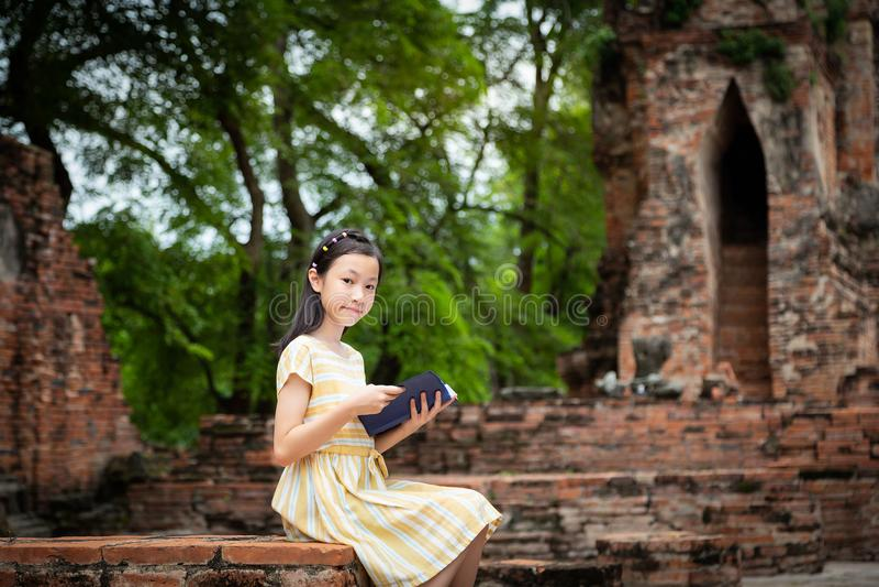 Muchacha linda asiática que se relaja al aire libre mientras que libro de historia leído, Studen foto de archivo libre de regalías