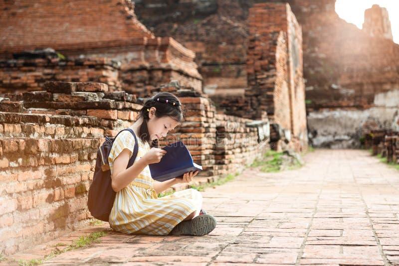 Muchacha linda asiática que se relaja al aire libre mientras que libro de historia leído, Studen fotografía de archivo libre de regalías
