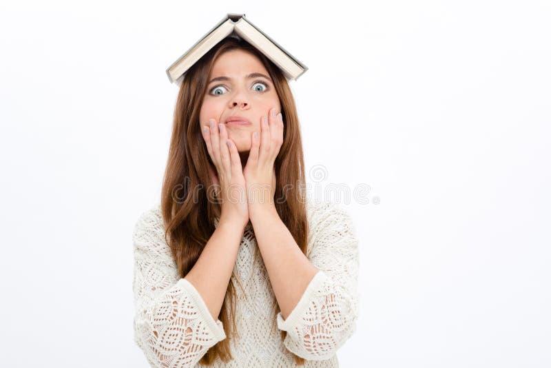 Muchacha linda asombrosa divertida con el libro abierto en su cabeza fotografía de archivo