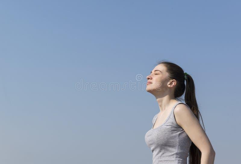 1 muchacha linda blanca con el pelo largo en soportes superiores grises con sus ojos cerrados contra el cielo azul imagen de archivo libre de regalías