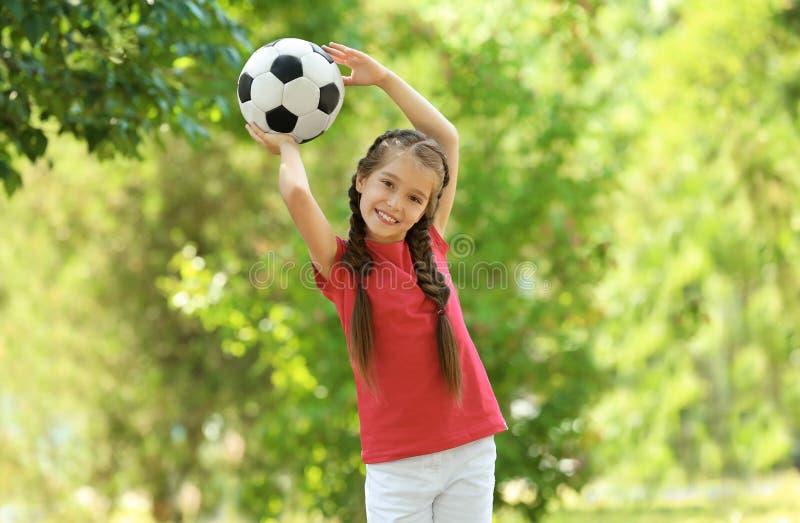 Muchacha linda con el balón de fútbol en parque imagenes de archivo