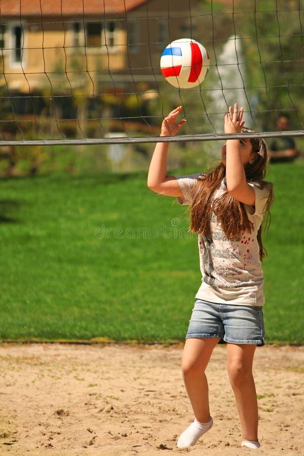 Muchacha linda con la bola cerca de la red del voleibol fotos de archivo