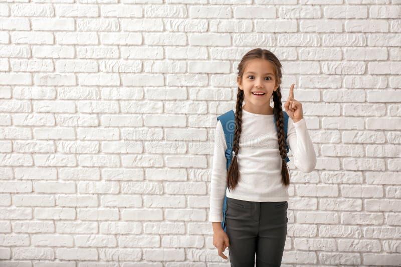 Muchacha linda con la mochila y el finger aumentado en el fondo blanco del ladrillo fotos de archivo libres de regalías