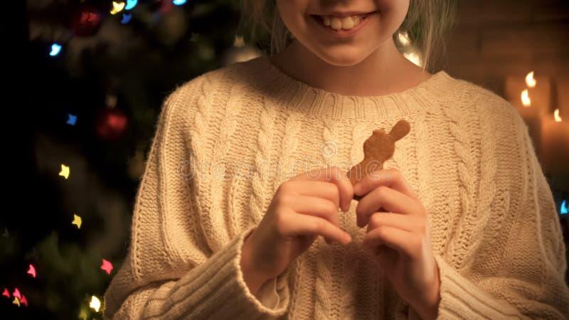Muchacha linda con la presentación sonriente del conejito de la galleta en la cámara en fondo iluminado foto de archivo libre de regalías