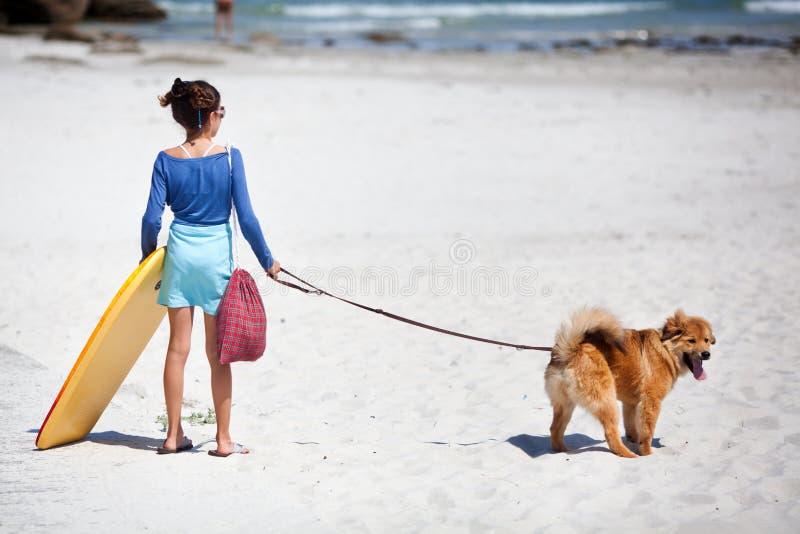 Muchacha linda con la tabla hawaiana y el perro en la playa imágenes de archivo libres de regalías