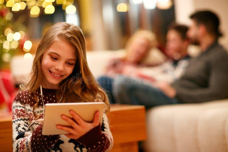 Muchacha linda con la tableta y los auriculares en casa fotografía de archivo libre de regalías