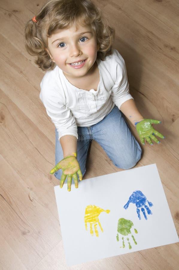 Muchacha linda con las manos coloreadas imagen de archivo