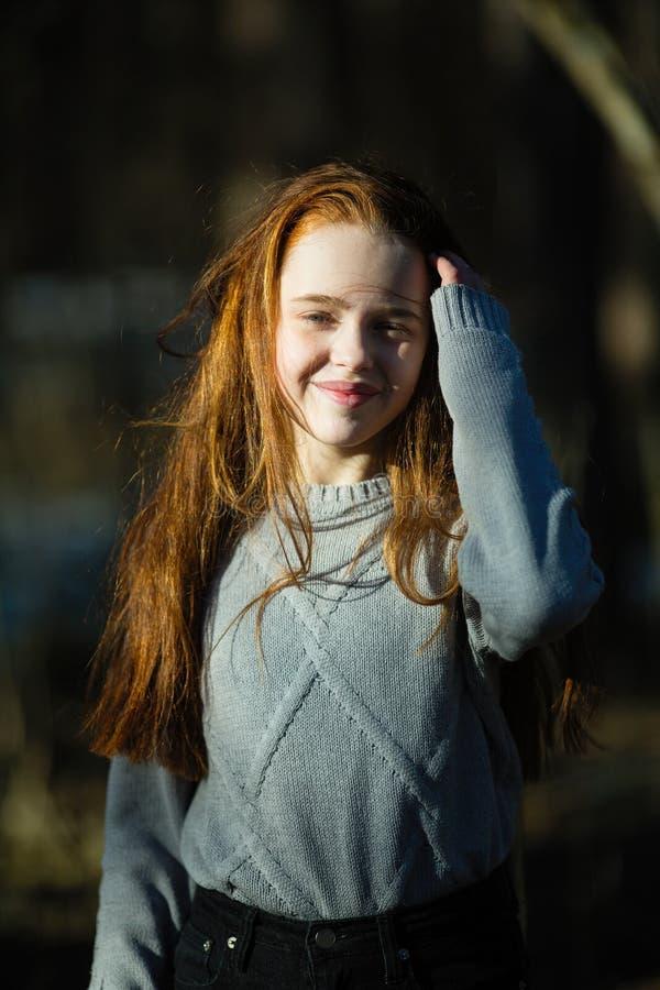 Muchacha linda de doce años con el pelo rojo ardiente que presenta en el parque del pino para un photoshoot imagenes de archivo