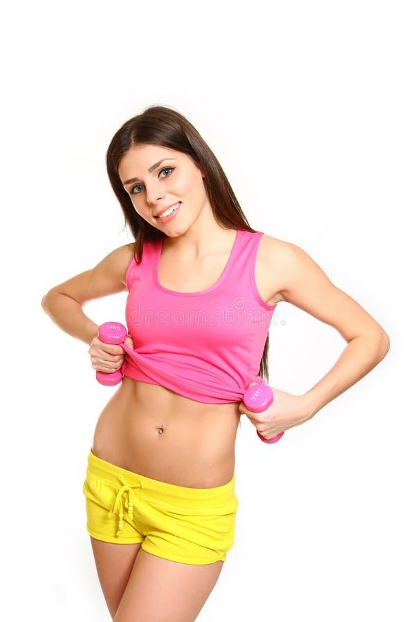 Muchacha linda de la aptitud con las pesas de gimnasia que muestran su vientre en la parte posterior del blanco imágenes de archivo libres de regalías