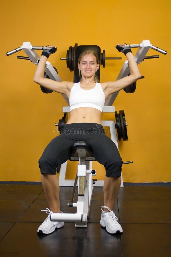 Muchacha linda de la aptitud que se resuelve en la gimnasia imagenes de archivo