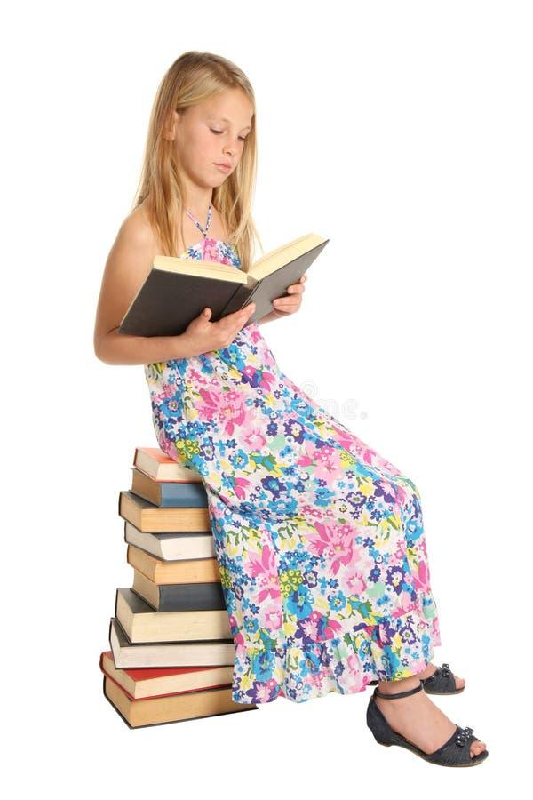 Muchacha linda de la escuela que se sienta en los libros fotografía de archivo libre de regalías