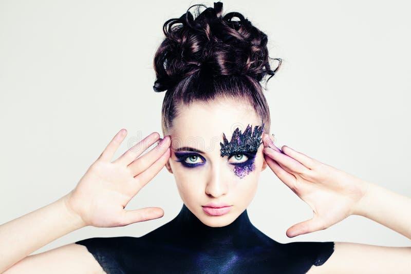 Muchacha linda de la moda con el peinado y el maquillaje creativos foto de archivo