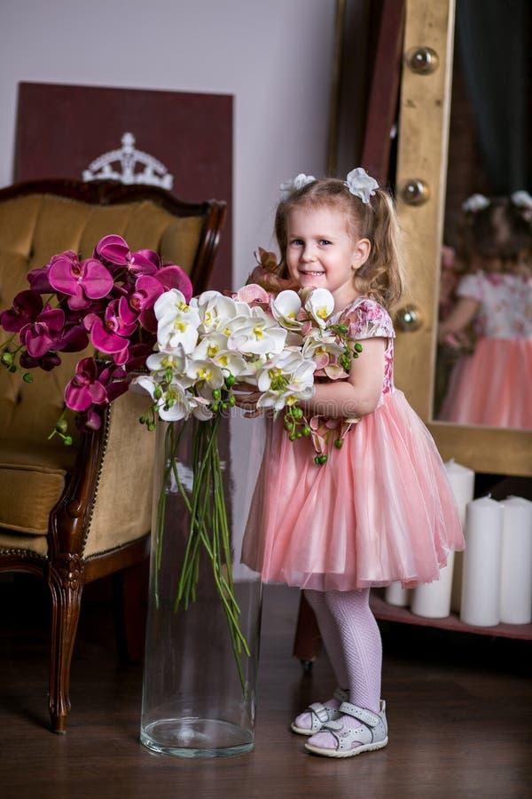 Muchacha linda de ojos azules en un vestido rosado que sostiene un florero con las orquídeas y la sonrisa fotos de archivo