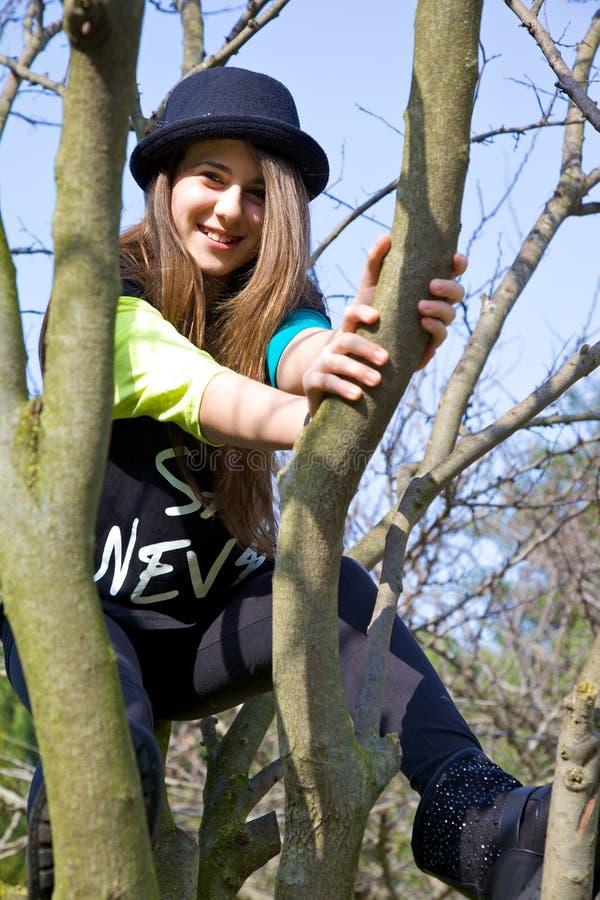 Muchacha linda del adolescente que se sienta en árbol con el sombrero imagen de archivo libre de regalías