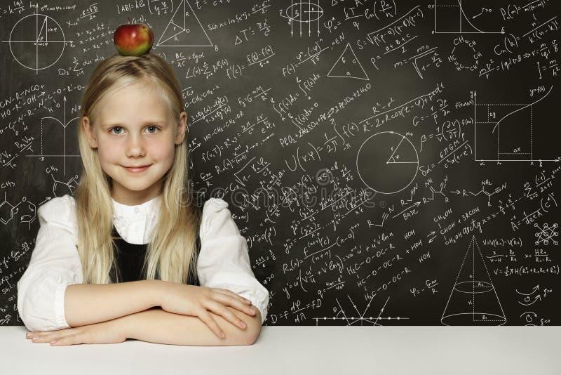 Muchacha linda del estudiante del niño con la manzana roja en la cabeza Fondo de la pizarra con fórmulas de la ciencia Aprendizaj foto de archivo libre de regalías