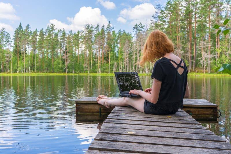 Muchacha linda del jengibre que se sienta en acera planked de madera y que trabaja con el ordenador portátil en día de verano con foto de archivo