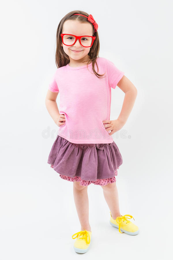 Muchacha linda del moda-tratante en marcos rojos rosados de los vidrios de la camiseta y de la falda del vestido fotos de archivo