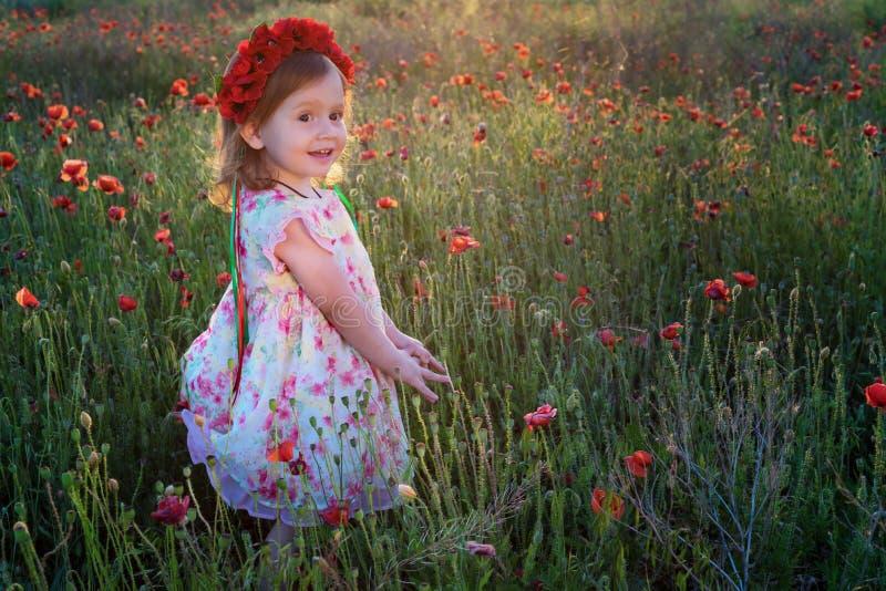 Muchacha linda del niño con la guirnalda de la flor en campo de la amapola imágenes de archivo libres de regalías