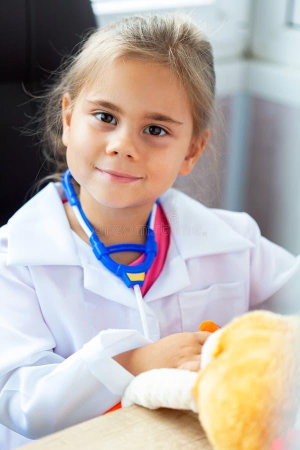 Muchacha linda del niño que juega al doctor con el juguete de la felpa foto de archivo