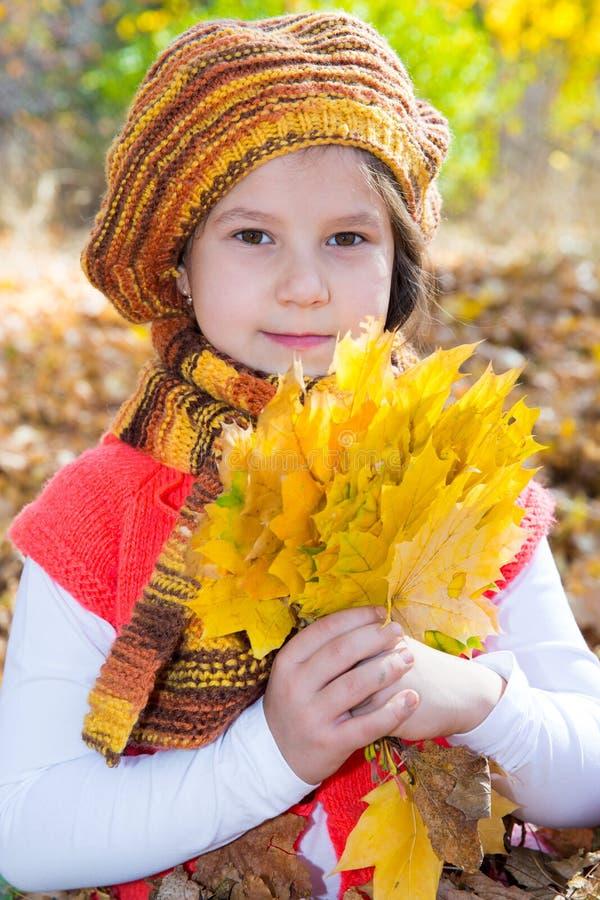 Muchacha linda del niño que juega con las hojas caidas fotografía de archivo
