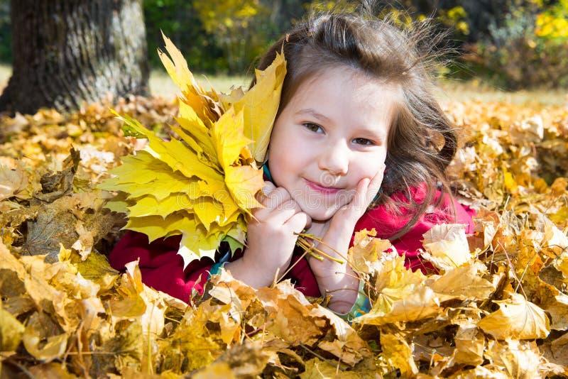Muchacha linda del niño que juega con las hojas caidas en otoño foto de archivo libre de regalías