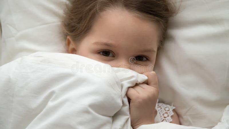 Muchacha linda del niño que mira la cámara debajo de la manta en cama fotografía de archivo libre de regalías