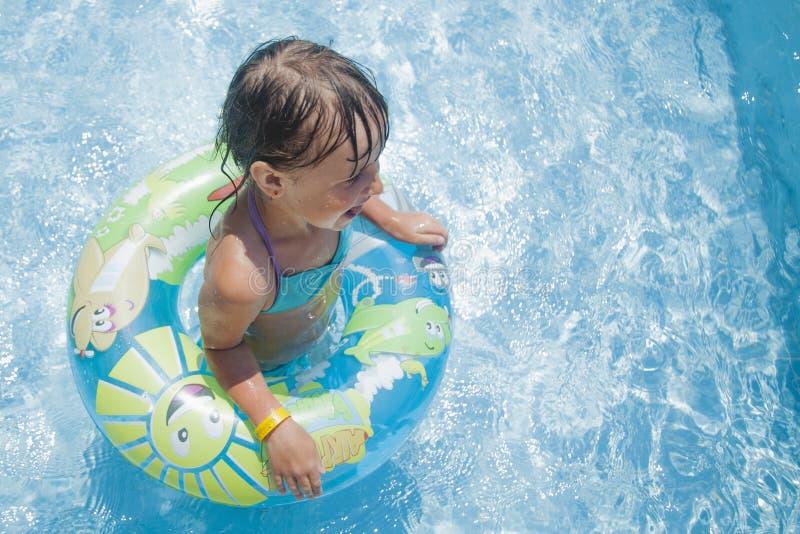 Muchacha linda del pequeño niño que se divierte y que juega en agua con el anillo colorido Vacaciones de verano y concepto sano d imágenes de archivo libres de regalías