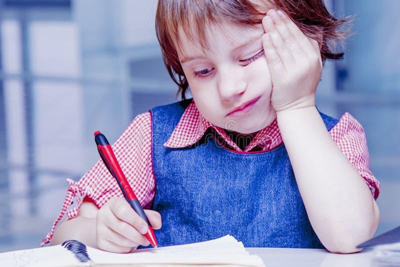 Muchacha linda del pequeño niño que tiene triste y aburrida mientras que aprende y m imagen de archivo libre de regalías