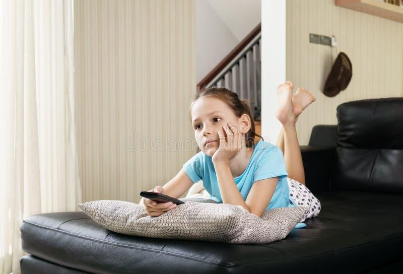 Muchacha linda del preadolescente que ve la TV en el sofá usando teledirigido Interior de la sala de estar en fondo foto de archivo libre de regalías